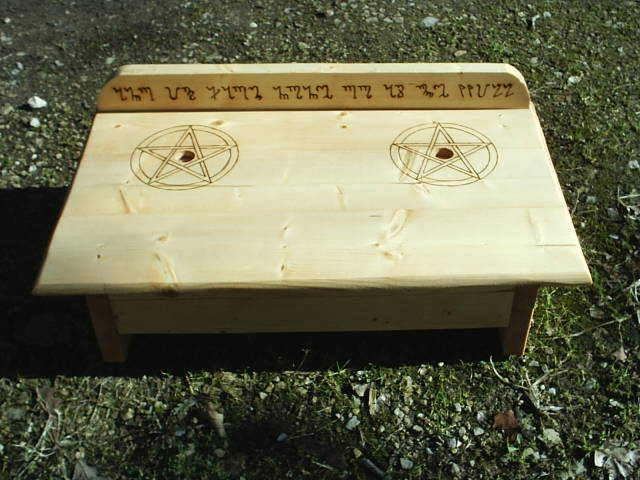 Two Pentacles surround candle holders and And It Harm None, Do As Ye Will is engraved on the backboard in Theban, the Witches Secret Language. And It Harm None, Do As Ye Will is a common Pagan verse, and is used often to symbolize a life of living with care for fellow persons, but without guilt of choice of our own destiny.
