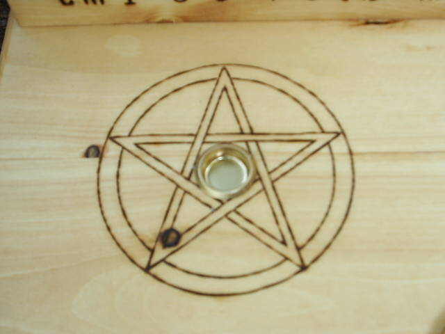 Two Candle Holders surrounded by wood-burned pentacles, and A Mounted Scrolled Pentagram in circle centered on table top of this Wooden Altar