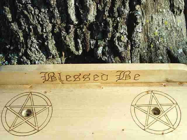 Two Pentacles surround candle holders and Blessed Be is engraved on the backboard.<br><br> Blessed Be is a common Pagan verse, and is used often in the parting of two or more Wiccans, in place of good-bye<border=